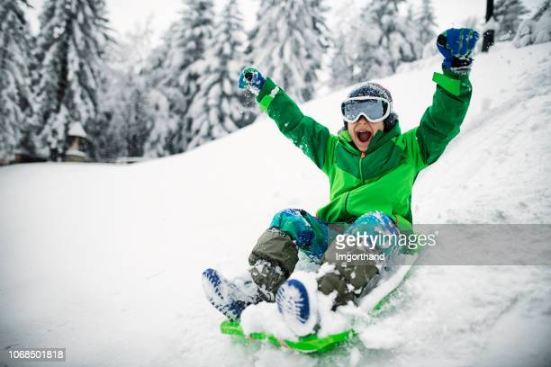 little boy sledding and shouting - sled stock pictures, royalty-free photos & images