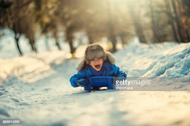 Little boy sledding and shouting