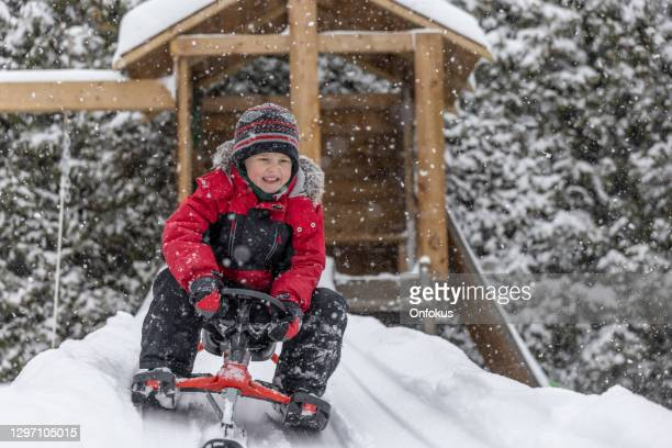 little boy sledding on the snow outdoors in winter - tobogganing stock pictures, royalty-free photos & images