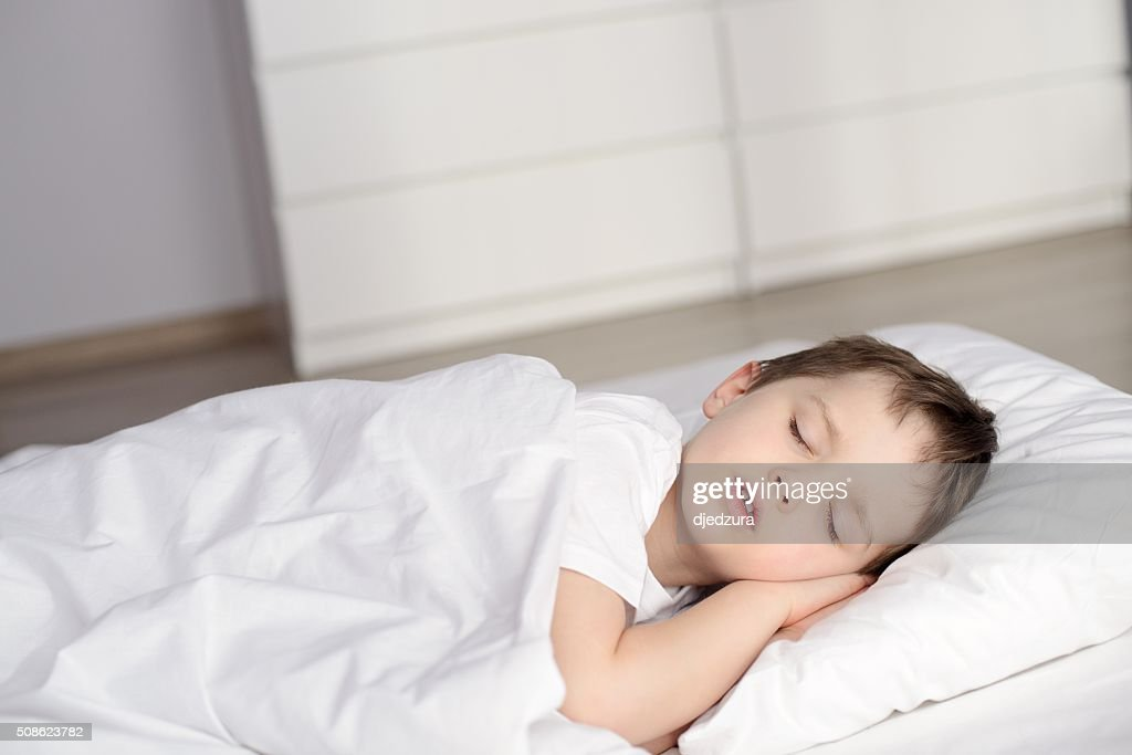Little boy sleeping in bed, happy bedtime in white bedroom : Stock Photo
