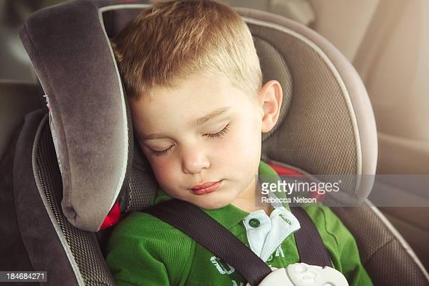 Little boy sleeping in carseat
