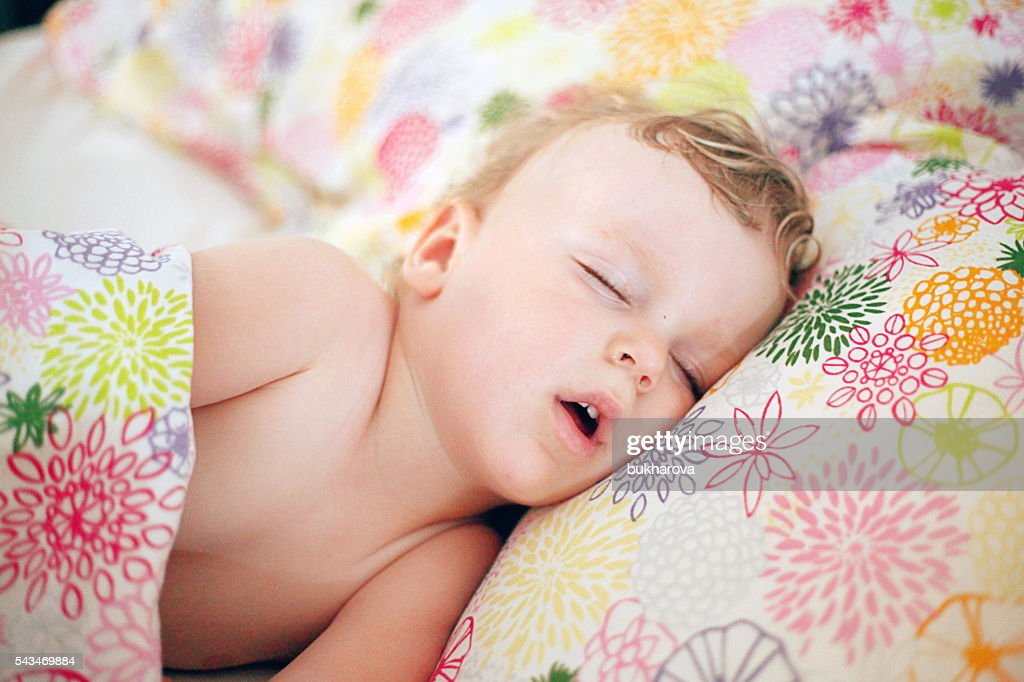 Little boy sleeping in the big bed : Stock Photo