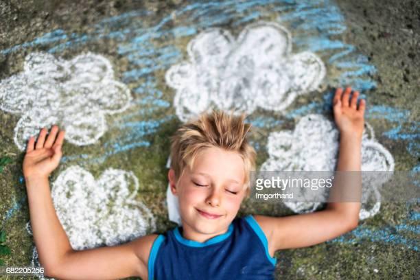 Niño durmiendo sobre las nubes pintadas.