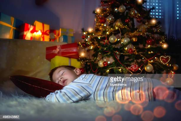 Little boy sleeping under the Christmas tree