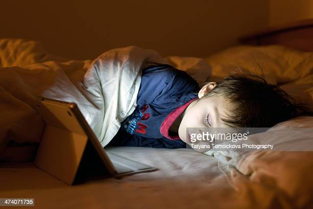 Little boy, sleeping with a tablet