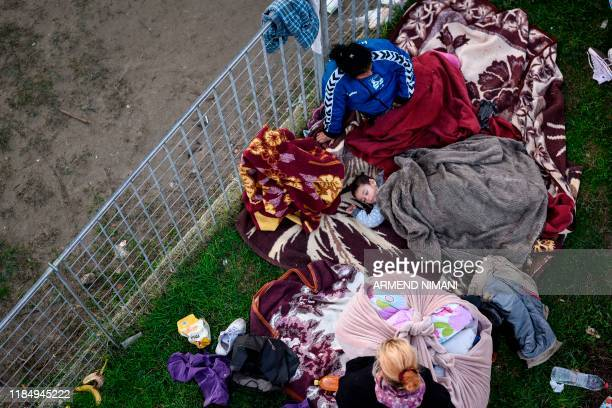 A little boy sleeps outdoors at a makeshift camp at the soccer stadium in Durres western Albania on November 27 after the strongest earthquake in...