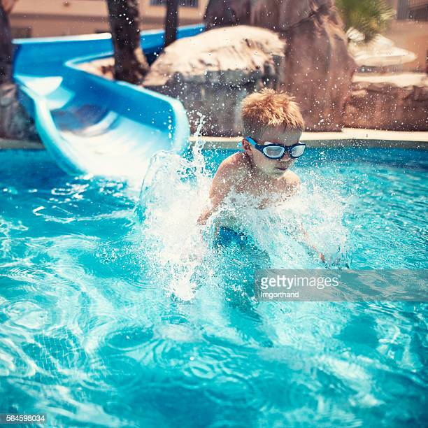 Little boy sliding and splashing in water park