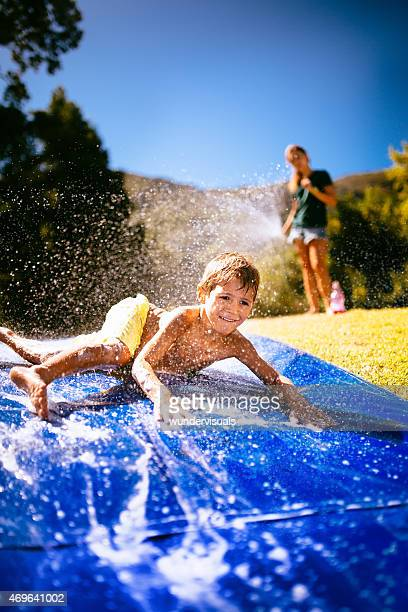 Little boy sliding down slippery water slide outdoors