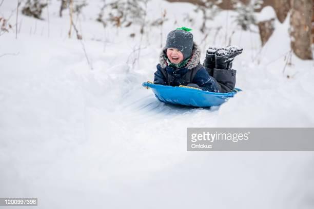 冬の雪の屋外で滑る小さな男の子 - 橇 ストックフォトと画像