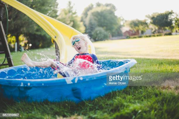 little boy sliding into kiddy pool - annie sprinkle stock pictures, royalty-free photos & images