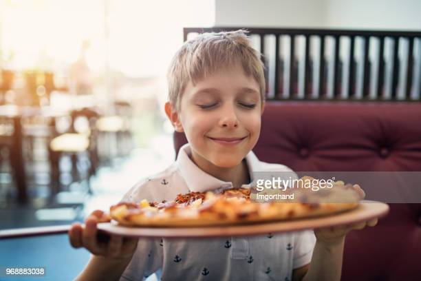 little boy smelling pizza in restaurant - food and drink stock pictures, royalty-free photos & images