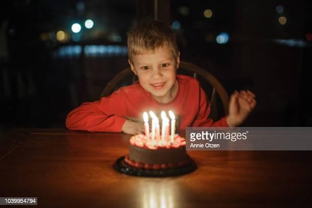 Little boy smiles at his birthday cake