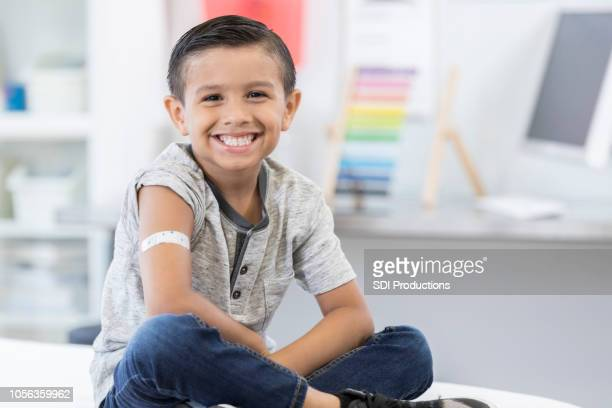 little boy smiles proudly at camera after vaccination - vaccination stock pictures, royalty-free photos & images