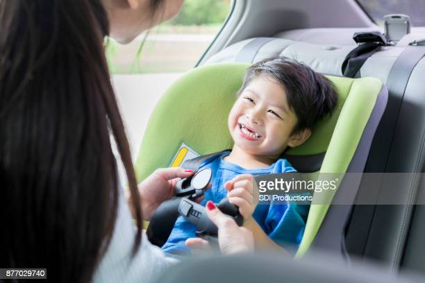 little boy smiles while mom straps him into booster seat - buckle stock pictures, royalty-free photos & images