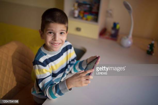 little boy smiles while playing with tablet - lerexis stock pictures, royalty-free photos & images