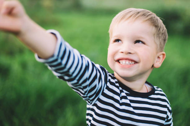 Little boy smiling   in a large field in the countryside