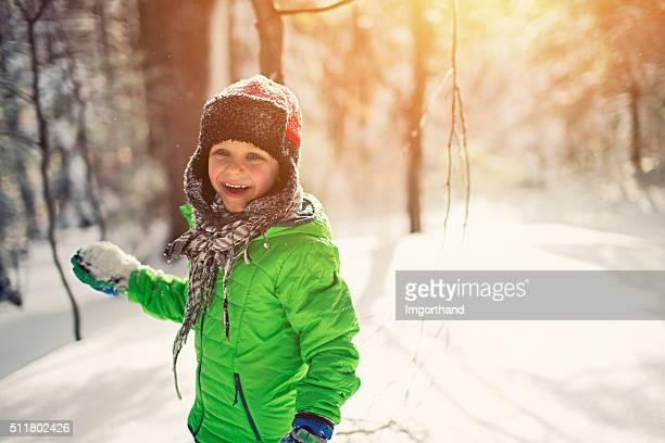 Kleine Junge Schneeballschlacht in sonnig Winter Wald