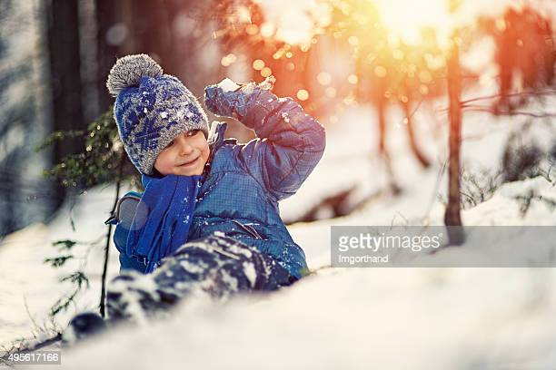 Petit garçon batailles de boules de neige dans la forêt d'hiver