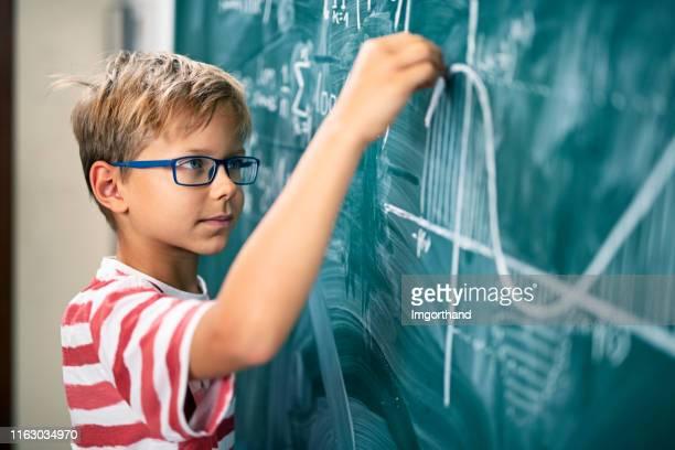 高度な数学的問題を解決する小さな男の子 - 数学記号 ストックフォトと画像