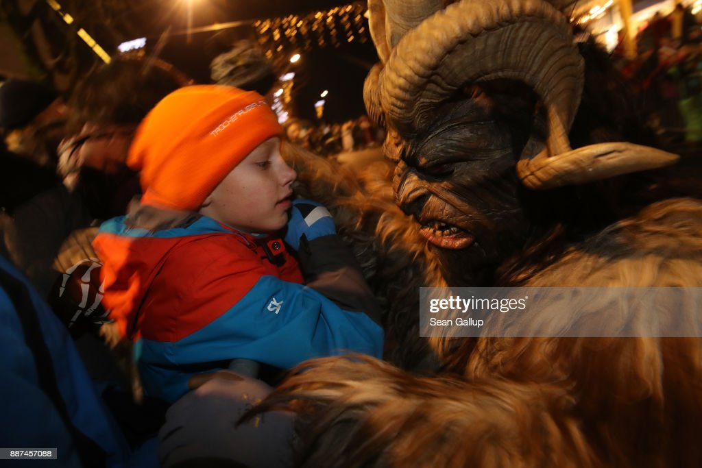 A little boy speaks to a devilish Krampus creature during the annual Krampus parade on Saint Nicholas Day on December 6, 2017 in Sankt Johann im Pongau, Austria. Several hundred Krampus creatures from the region took part in this year's Sankt Johann parade. Krampus traditionally accompanies Saint Nicholas and angels in a house to house procession to reward children who have been good and warn those who have not, though in recent decades Krampus parades have become an intrinsic part of local folklore and take place throughout the end of November and into the first half of December in the alpine regions of Germany, Austria and Italy. Krampus usually wears large cowbells on his back that he rings by shaking his hips to ward off the evil spirits of winter. He also carries a switch made of branches or animal hair that he uses to whip bystanders.