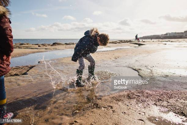 little boy splashing in a puddle - whitley bay stock pictures, royalty-free photos & images