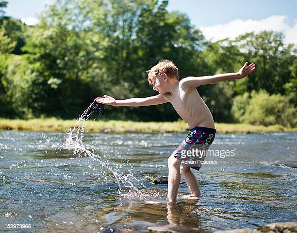 little boy splashing in river