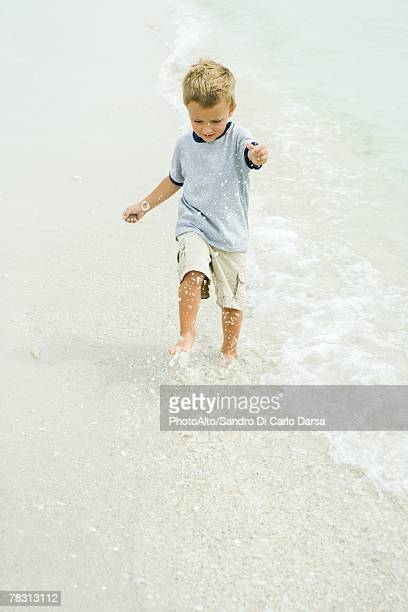 Little boy splashing in surf on beach, full length