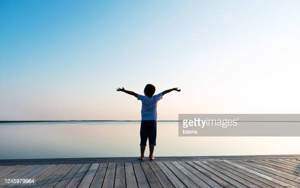 little boy standing at lakeside with arms outstretched - one boy only stock pictures, royalty-free photos & images