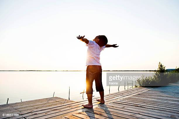 Little boy standing at lakeside with arms outstretched