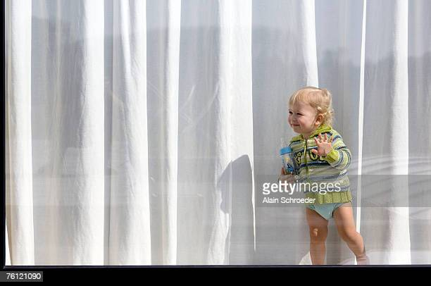 Little boy standing behind window