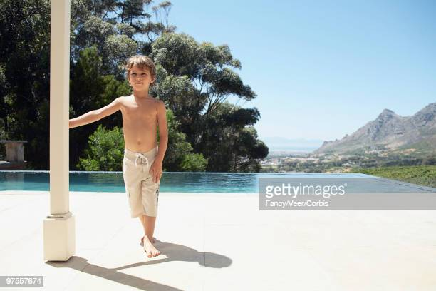 Little boy standing by swimming pool