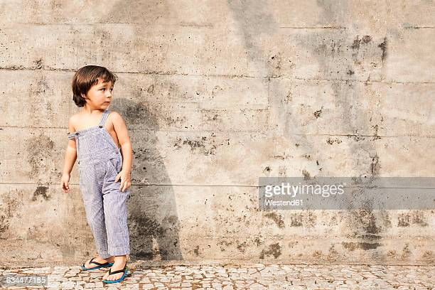 Little boy standing in front of concrete wall in summer