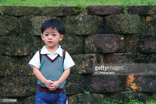 Little boy standing in front of stone wall