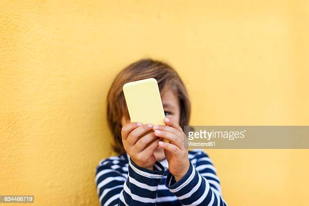 Little boy standing in front of yellow wall playing with smartphone