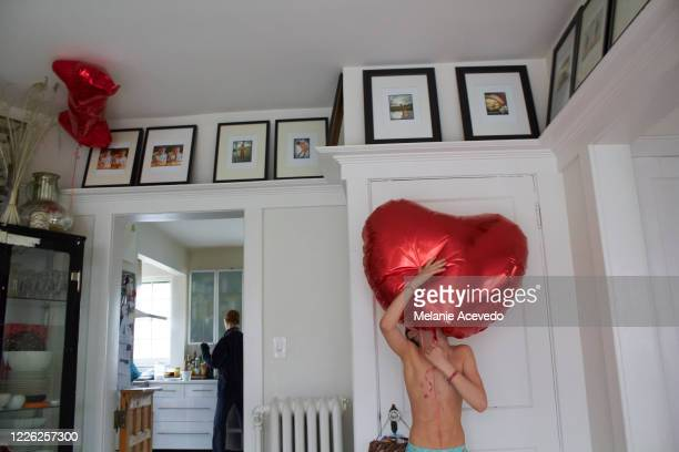 little boy standing in his living room holding up a big red heart shaped balloon in front of himself. sister in kitchen in the background of image - anniversaire humour photos et images de collection