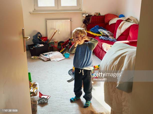 little boy standing in his messy room building cross with his fingers - chaos stock-fotos und bilder