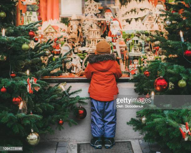 little boy  standing near christmas tree in rothenburg - store window stock pictures, royalty-free photos & images
