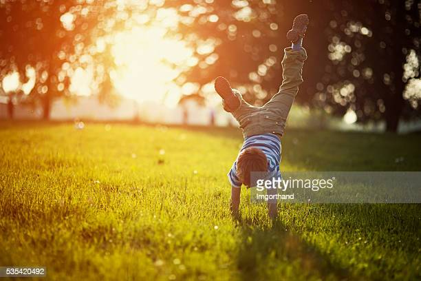 little boy standing on hands on grass - zonlicht stockfoto's en -beelden