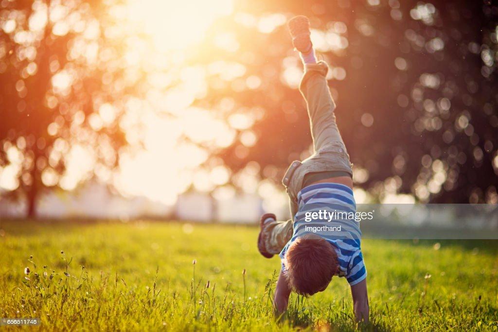 Little boy standing on hands on grass : Stock Photo