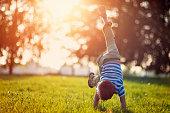 Little boy standing on hands on grass