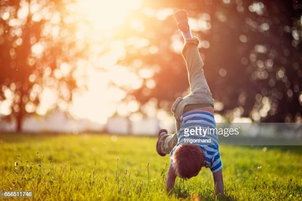 Little boy standing on hands on grass