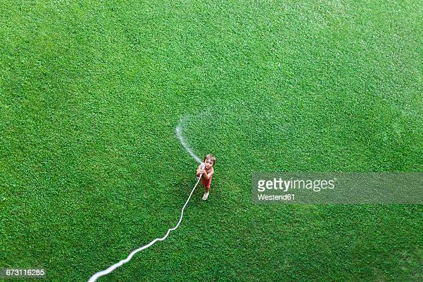 Little boy standing on lawn playing with garden hose, top view