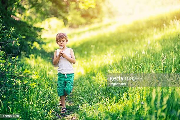 Kleine Junge auf einem Bein und Blasen Löwenzahn