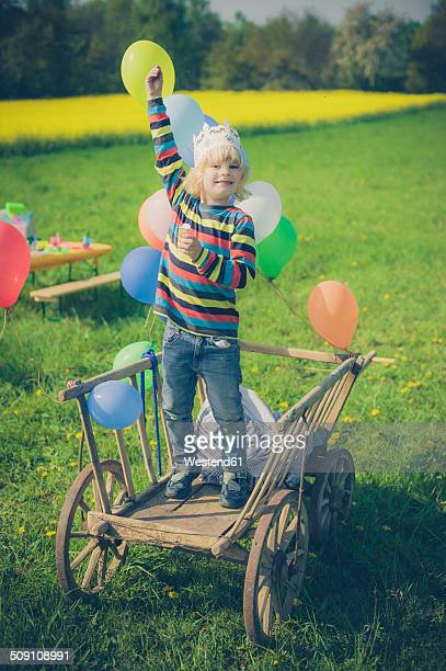 Little boy standing on wooden trolley holding ballons