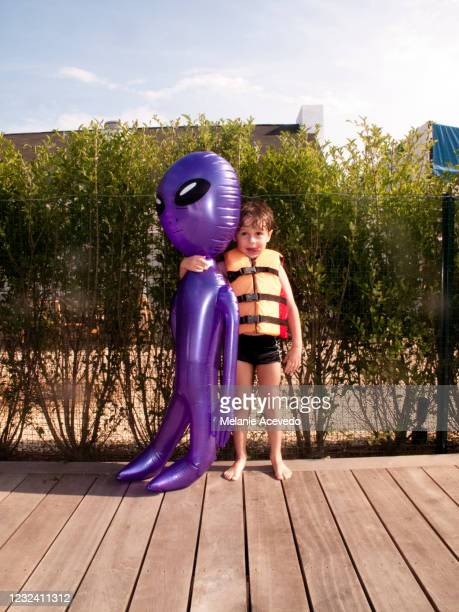 little boy standing outside by a pool in an orange life vest holding onto a purple blow up toy that is bigger than he is. - blow up doll stock pictures, royalty-free photos & images
