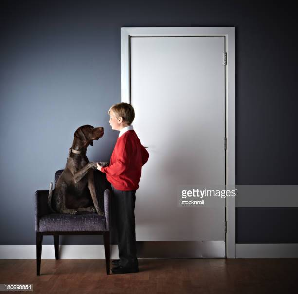 Little boy standing with dog outside vets door