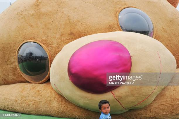 TOPSHOT A little boy stands in front of a giant teddy bear measuring more than 20 meters long and 4 tons of weight which entered the Guiness Book of...