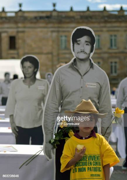 A little boy stands in front of a lifesize image of a killed or missing member of the Patriotic Union displayed during a tribute to the victims of...