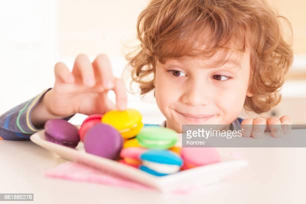 little boy stealing cookies - solo un bambino maschio foto e immagini stock