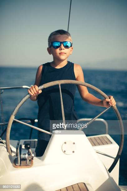 Little boy steering with sailboat
